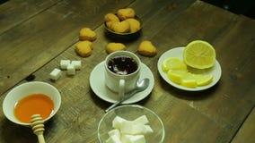 La main femelle met des morceaux de sucre dans une tasse de thé noir fraîchement brassé banque de vidéos