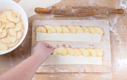 La main femelle met des tranches de pomme sur la bande de la pâte sur un bois léger Photographie stock libre de droits