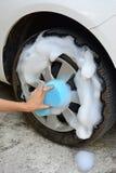 La main femelle nettoie le pneu de voiture avec l'éponge bleue Photos stock
