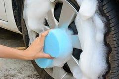 La main femelle nettoie le pneu de voiture avec l'éponge bleue Images libres de droits