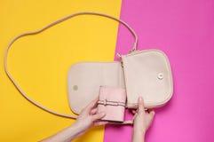 La main femelle prend le portefeuille en cuir du sac sur un fond en pastel images libres de droits