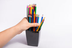 La main femelle prend les crayons de couleur de la boîte sur le fond blanc Copiez l'espace pour le texte Image libre de droits