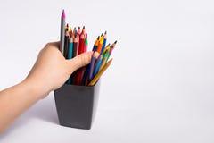 La main femelle prend les crayons de couleur de la boîte sur le fond blanc Copiez l'espace pour le texte Images stock