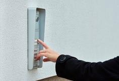 La main femelle presse une sonnette de bouton avec l'interphone image libre de droits