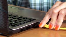 La main femelle relient le câble LAN d'Internet à l'ordinateur portable closeup banque de vidéos