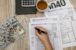La main femelle remplit feuilles d'impôt 1040 sur une table en bois photos stock