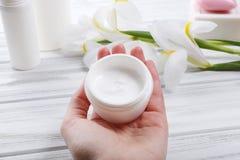 La main femelle tenant la crème cosmétique dans le pot en verre, se ferment  Photographie stock