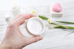 La main femelle tenant la crème cosmétique dans le pot en verre, se ferment  Photos stock
