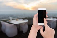 La main femelle tenant un téléphone sur la table de dîner trouble a placé avec le soleil Image stock