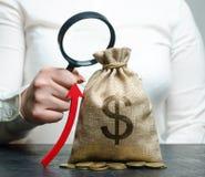 La main femelle tient la loupe au-dessus du sac et de la flèche d'argent Analyse de concept des bénéfices et du budget à la socié images stock