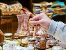 La main femelle tient un verre turc de thé de souvenir avec une cuillère image stock