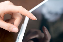 La main femelle touche une tablette blanche d'affaires sur un support Image libre de droits