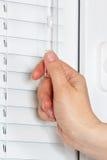 La main ferme les abat-jour sur la fenêtre en plastique blanche Photo libre de droits