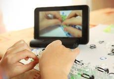 La main font le jouet de métier à tisser d'arc-en-ciel avec la leçon en ligne sur la tablette Photo stock