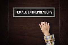 La main frappe sur la porte femelle d'entrepreneurs Photo stock