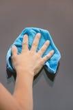 La main frotte le verre, tissu bleu Images libres de droits