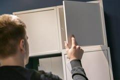 La main haute étroite ouvre la chambre à coucher d'étagère à la maison recherchant les choses f image stock