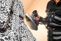 La main haute ?troite de femme lisse la robe avec du fer de vapeur sur un mannequin image stock
