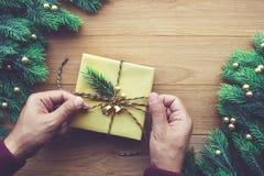La main humaine décorant le boîte-cadeau présente avec la branche de pin sur la table en bois Image stock