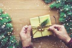 La main humaine décorant le boîte-cadeau présente avec la branche et les chutes de neige de pin sur en bois Photo libre de droits