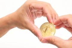 La main humaine du ` s formant le symbole de coeur contre le bitcoin d'or de cryptocurrency sur le blanc a isolé le fond Conce nu Photo stock