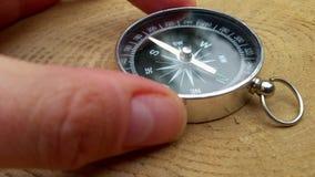 La main humaine et prend la boussole détermine la direction du monde sur le fond du bois de chanvre, plan rapproché clips vidéos