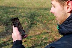 La main humaine jugeant le téléphone intelligent cassé a fendu l'écran endommagé Photographie stock