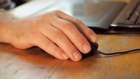 La main humaine met en rouleau la roue de souris près du clavier et de la tablette noirs Main de l'homme s'étendant sur la souris banque de vidéos