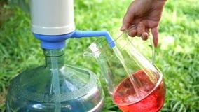 La main humaine remplit cruche transparente de l'eau froide à partir d'une grande bouteille ou refroidisseur de pompe à eau Contr banque de vidéos