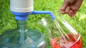 La main humaine remplit cruche transparente de l'eau froide à partir d'une grande bouteille ou refroidisseur de pompe à eau Contr clips vidéos