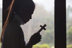 La main humaine tient la croix concept de prière pour la foi, la spiritualité et le concept chrétien de religion photographie stock