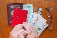 La main humaine, verres, et un certificat de pension sur la traduction en bois de surface-le dans le Russe : certificat supérieur Photographie stock libre de droits
