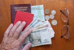 La main humaine, verres, et un certificat de pension sur la traduction en bois de surface-le dans le Russe : certificat supérieur Image stock