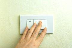 La main humide tournent sur le commutateur électrique de lumières sur le fond en bois de mur photographie stock libre de droits