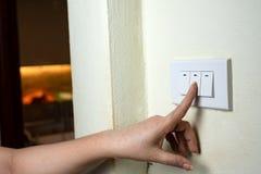 La main humide tournent sur le commutateur électrique de lumières sur le fond en bois de mur image libre de droits
