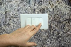 La main humide tournent sur le commutateur électrique de lumières sur le fond en bois de mur image stock