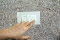La main humide tournent sur le commutateur électrique de lumières sur le fond en bois de mur photos stock