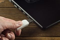 La main insère une commande d'instantané d'USB de blanc dans l'entrée d'un ordinateur portable noir, plan rapproché, affaires photographie stock libre de droits