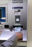 La main insérant le billet de banque dans l'argent comptant distribuent Images stock