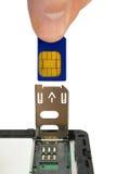 La main installent la carte de sim Image libre de droits