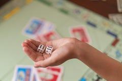 La main jette des matrices de jeu sur le fond du terrain de jeu photos stock