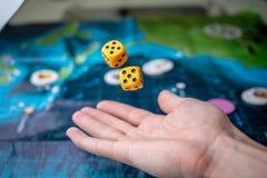 La main jette deux matrices jaunes sur le terrain de jeu Chance et excitation Jeux de soci?t? Moments de jeu dans la dynamique photographie stock