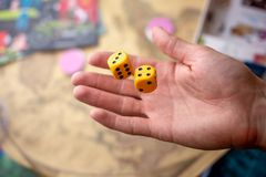 La main jette deux matrices jaunes sur le terrain de jeu Chance et excitation Jeux de soci?t? Moments de jeu dans la dynamique photos stock