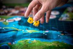 La main jette deux matrices jaunes sur le terrain de jeu Moments de jeu dans la dynamique Chance et excitation Strat?gie de jeux  image stock