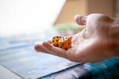 La main jette deux matrices jaunes sur le terrain de jeu Moments de jeu dans la dynamique Chance et excitation Strat?gie de jeux  photo stock