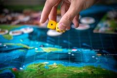 La main jette deux matrices jaunes sur le terrain de jeu Moments de jeu dans la dynamique Chance et excitation Strat?gie de jeux  photos libres de droits