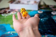 La main jette les matrices jaunes sur le terrain de jeu Chance et excitation Concept des jeux de soci?t? Moments de jeu dans la d image stock