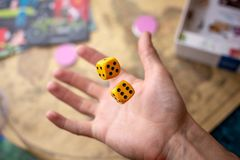 La main jette les matrices jaunes sur le terrain de jeu Chance et excitation Concept des jeux de soci?t? Moments de jeu dans la d image libre de droits