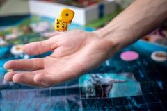 La main jette les matrices jaunes sur le terrain de jeu Chance et excitation Jeux de société de concept photographie stock