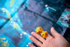 La main jette les matrices jaunes sur le terrain de jeu Chance et excitation Jeux de société de concept photo libre de droits